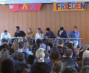 Sieben SchülerInnen des Gemeinschaftskunde-Leistungskurses diskutieren mit ihren MitschülerInnen